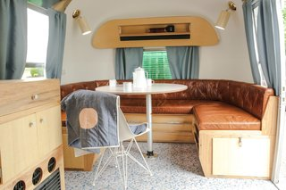 This renovated 1965 Airstream Overlander Land Yacht elevates #vanlife with midcentury-inspired furnishings. While the roving home is reminiscent of a Wes Anderson film, it maintains a streamlined sense of minimalism with furnishings that fold away to create space in the compact vehicle. Custom fabricator Eoin Murphy and designer Robin Grundy-Murphy designed this airstream with entertaining in mind. A magazine rack found originally on the wall of the Airstream was replicated at the bottom of the dining banquette—which also converts into a double bed.
