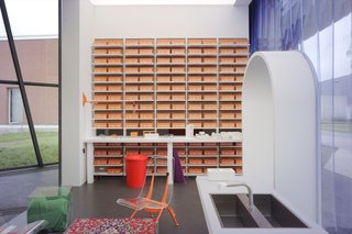"""A wall in """"Tomorrow"""" comprises consecutively numbered bright orange Ceramic Blocks that double as storage."""