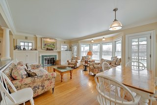 The family room is anchored with a fireplace on one side and a breakfast table on the other. Two glazed doors to the rear deck flank the large window seat.