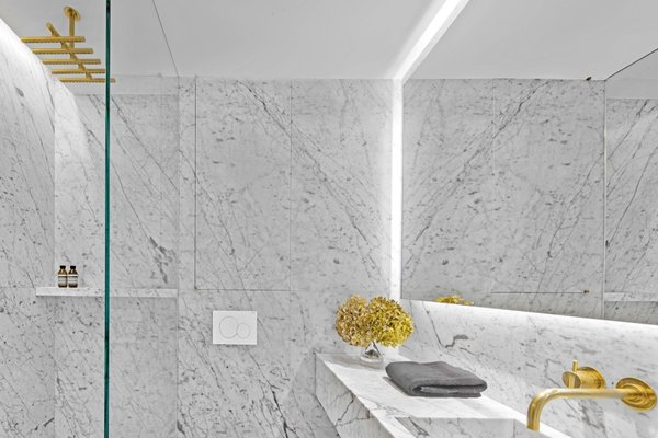 Slabs of Carrara marble cover the minimalist bathroom, which is punctuated with fixtures made from unlacquered brass.