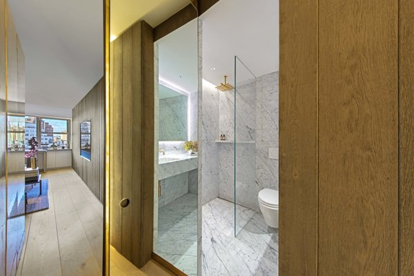 Opening the mirrored door reveals a surprising contrast of colors and materials between the bathroom and the timber-lined living space.