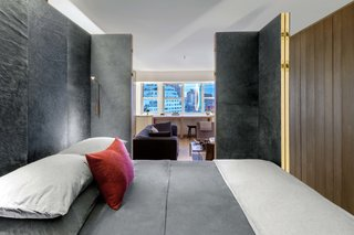 The walls of the brass bedroom cube fold back to reveal the living room on one side and the entry hall on the other.