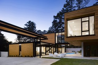 """""""New versus old can be decoded where the original yellow brick is exposed and seen in contrast to new cypress siding and white stucco surfaces,"""" note the architects. """"The black color of the original wood, post-and-beam structure is extended to the new, exposed black steel."""""""
