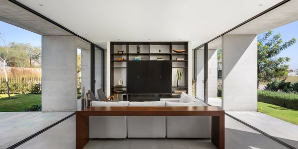 Since the clients wanted to host large social gatherings, the architects designed an open-plan living room and dining area that expands seamlessly to the outdoors.