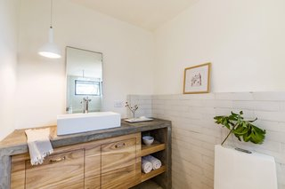 The stylish and cost-effective bathroom features a concrete countertop, subway tiling, and laurel plywood cabinetry.
