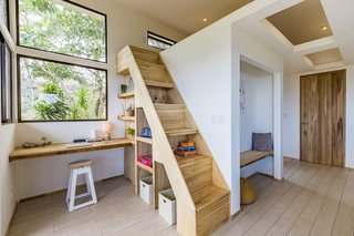The light-filled office overlooks stunning views. The stairs to the loft include built-in storage and shelving—a space-saving solution inspired by the couple's experience living in a tiny house.