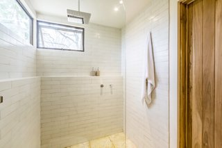 Subway tiling wraps around the enclosed shower, while operable windows provide airflow without compromising privacy.
