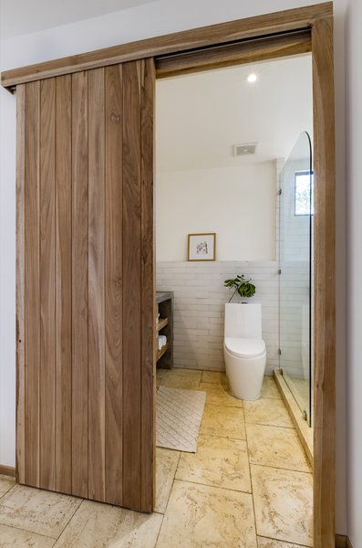 To the right of the entrance, sliding tongue-and-groove laurel plywood doors open up to reveal the bathroom.