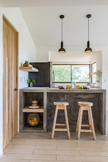 The breakfast bar from the original home was given a modern refresh. The existing stools were refinished and paired with concrete countertops. Designer pendant lights hang from above.