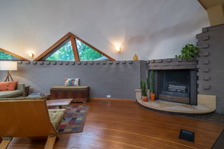 The living and dining area is anchored by a recently rebuilt curved brick fireplace.