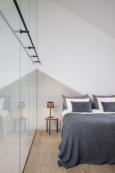 The guest bedroom features integrated wood cabinetry and 15-foot-tall frameless glass panels.