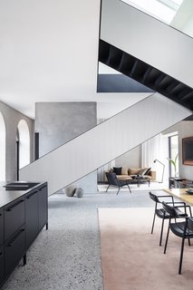 The modern steel staircase adds a striking architectural element to the space and leads from the ground-floor living spaces to the bedrooms upstairs.