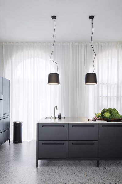 Vipp pendant lamps ($500) are suspended over the sleek and modular Vipp kitchen. The iconic pedal bin occupies a corner.