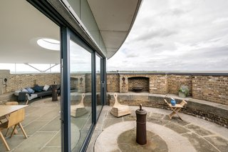 Full-height sliding glazed doors open up to an outdoor terrace on the exposed section of the battlements with spectacular views.