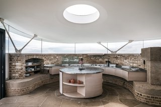 The well-appointed kitchen includes all the modern necessities for entertaining. A band of glazing wraps around the open-plan living space to take in panoramic views.
