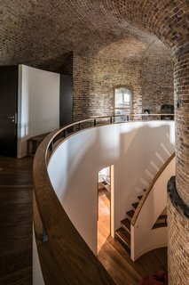 A curved staircase descends to the ground-floor bedrooms.