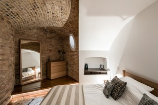 Light wells cut into the nearly 10-foot-wide masonry walls let daylight into the bedrooms, which were formerly used as storage rooms.