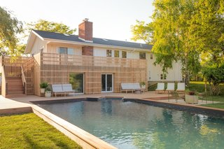 The backyard features a large pool with a mahogany wrap-around deck and the Perch Sofas and coffee table from Blu Dot's new outdoor furniture collection.