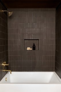 Accessible from both the Green Room and the Pool House, the dark-toned guest bath features tiled walls by Heath Ceramics, a tub and sink by Duravit, and fixtures by California Faucets.