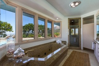 A peek inside the master bath with views of the pool and Santa Barbara.