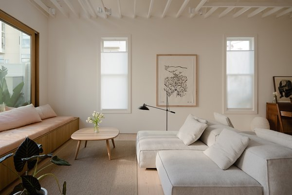 The living room of the remodeled Front House is furnished with an Extrasoft sofa by Piero Lissoni. The coffee table is part of the Nomad Collection by Jacob May Design in collaboration with Heath Ceramics.
