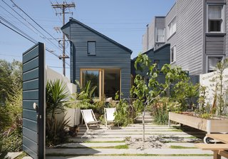 """The darker, midnight blue exterior paint color was used on all of the existing building elements to create more of a dynamic contrast with the new structure, which was painted white,"" says Ryan. Tomatoes, little gem lettuce, green beans, a tobacco plant, and a few strawberry bushes (tended by the kids) grow in the courtyard."