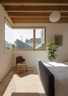 The corner window bathes the master bedroom in natural light, while exposed rafters and bleached Douglas Fir floors lend a sense of warmth.