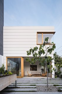 """""""The custom profile painted siding echoes the typical horizontal lap siding seen throughout the neighborhood while playing with scale,"""" says Ryan. """"Also, the extruded white oak window boxes on the new structure give a nod to the more traditional approach to window casings while making them more three dimensional."""""""