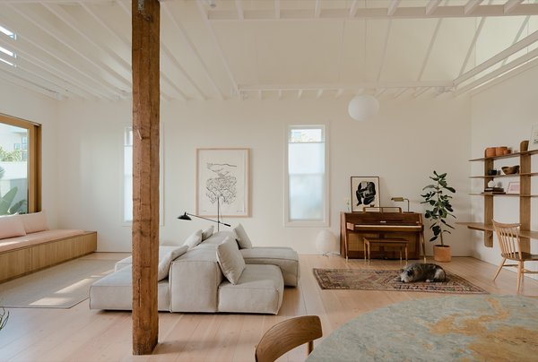 The existing wood structure and ceiling of the former saloon were completely refinished, and the exposed rafters were painted white for a brighter and more spacious feel. The old windows, floors, and finishes were replaced to create consistency with the new house.