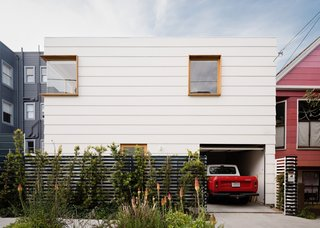 A view of the newly constructed modern Back House seen from the street. Custom redwood fencing wraps around the home.