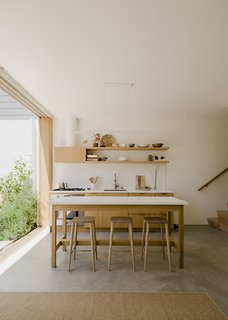 Ryan Leidner designed the kitchen island/dining table, which was built by a cabinetmaker out of white oak plywood and Neolith countertops.