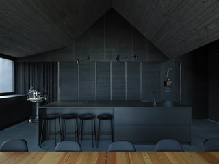 The dark kitchen creates a bold visual contrast with the nearby cirmolo wood wall. The kitchen countertops are slate, and the cabinets are dark gray-painted European oak.