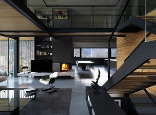 A glass-walled bridge links the master bedroom with the office on the upper floor. The layout creates a double-height space for the living area and keeps the drama of the exposed concrete ceiling visible from the ground floor.