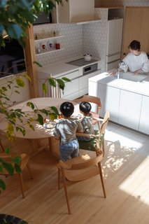 Artificial white marble by Panasonic lines the backsplash and countertops in the kitchen. The open-plan layout lets the wife keep an eye on her children at all times.