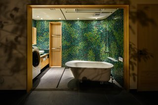Vibrant mosaic tile laid by a local craftsman cover the bathroom walls. Made from six different shades of green, the forest-like mural is another way the home brings nature indoors.