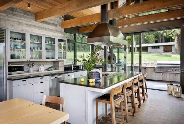 The centrally located kitchen is the heart of the home and the prime gathering space. Glazed sliding doors open the space up to the BBQ patio and the beach-facing patio (not pictured here). Note the outdoor pizza oven that's enclosed in a salvaged and modified steel buoy—a nod to the multiple smokers and stoves made of steel buoys originally found on the property.