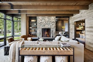 """The steel-and-wood beam details in the living room, dining room, and kitchen are a nod to the fact that the big open span facing the water is achieved with a large steel beam up in the ceiling from which all those large wood beams are suspended,"" notes the firm. The natural materials palette in the interior includes Pioneer Millworks 'Prairie' reclaimed wood siding for the walls, stained clear vertical grain cedar ceilings (main level), and solid end grain hemlock flooring by Oregon Lumber."