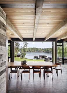 """As you enter, you turn and the beams direct your attention to the view through the dining room to the water,"" notes DeForest. ""As the floor steps down, the living spaces open up to a generous scale that is fully open to the view and the outdoor terrace."" The dining chairs are from Case Furniture sourced from Design Within Reach."
