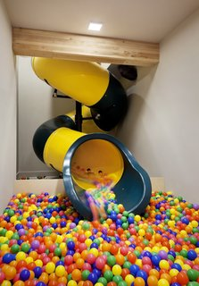 After the clients discovered the location of the slide, they decided to add a ball pit in the basement where the slide empties out.