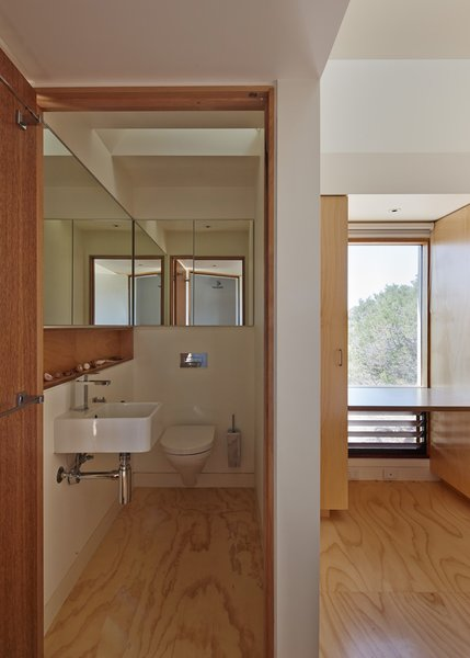 A long line of mirrors makes the compact bathroom feel more spacious.