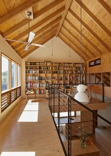An office on the mezzanine level includes a custom-made cantilevered bookcase by Orana. The lights are Beacon Lighting bulbs with Fat Shack Vintage ceiling light cords.