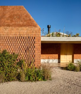 """""""The house portrays a dual condition reflected in the materials: brick on the outside, and concrete and wood on the inside,"""" says architect Fernanda Canales. """"The red color and the rough texture of broken brick on the outside accentuate a completely different condition than the smooth and neutral interior."""""""