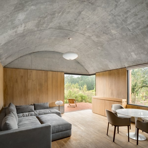 A family room caps the southern end of the bedroom wing and, as with all the bedrooms, features an exposed concrete barrel vault ceiling and opens up to an east-facing outdoor patio.