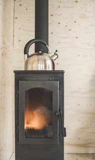 The Werkstattofen wood stove, which can be found in hardware stores across Northern Europe, transfers heat quickly and can heat the cabin up in less than 15 minutes. Not pictured is the double-layered metal sheeting that wraps around the stove for fire protection.