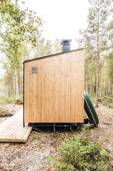 At the far end of the cabin, the duo installed this Finnish necessity: the sauna. The multipurpose space can be accessed through the bedroom or via the outdoor terrace. It serves as a multipurpose space where they can also cook food—such as pike fished from the lake.  Photo 13 of 20 in Students Build a Tiny Prefab Cabin in the Woods For Less Than $14K