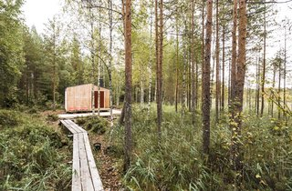 Built with trees felled on-site, a 650-foot-long elevated pathway connects the cabin to the nearest road.