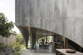 Filled with light and views of greenery, two exquisitely crafted concrete pavilions form an award-winning home that ages elegantly over time. The bold, monolithic designs of Australian architecture studio Edition Office have been brought to life in an unexpected place—Hawthorn, one of the most affluent suburbs in Melbourne that's better known for Victorian architecture than contemporary design. The recently completed home—dubbed the Hawthorn House—was created for a couple who asked Edition Office directors Kim Bridgland and Aaron Roberts to apply the design sensibilities they would normally use for rural landscapes to a more suburban context. In contrast to the soft greenery, the home is sheathed and supported by board-formed concrete, a material suggested by the client, who drew on his background in construction during the highly collaborative design process.