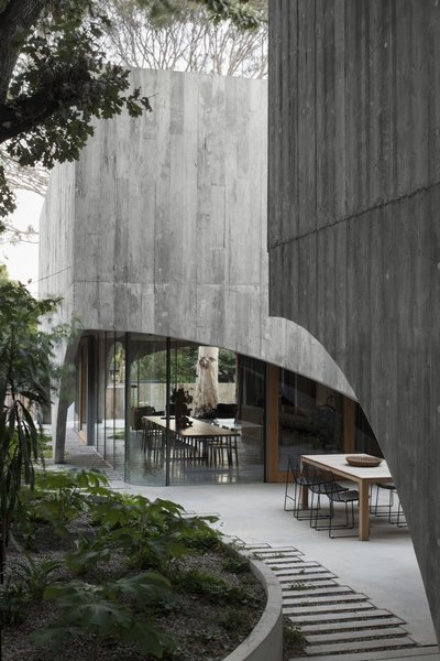 A north-facing courtyard and garden sits between the two concrete pavilions.