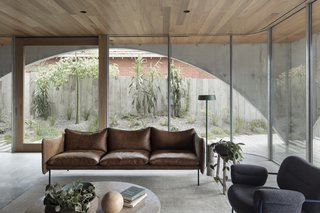 A warm timber palette, rounded surfaces (note the rounded corners in the custom double-glazed walls), and a rich variety of textures lend warmth to the minimalist concrete home.