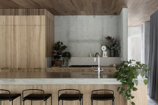 Blackbutt veneer cabinetry inject warmth into the kitchen and match the blackbutt ceiling planks seen throughout. Granite and concrete countertops create visual breaks in the timber surfaces.
